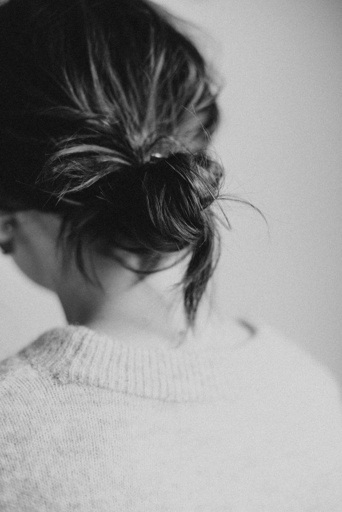 Black and white photo of the back of a woman. She is dressed in a sweater and has her hair in a low messy bun that touches the back of her neck.