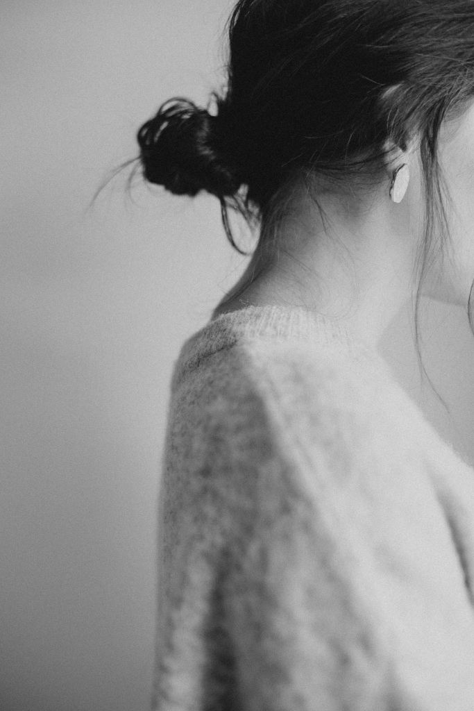 Side profile of a woman dressed in a sweater and low messy bun. Her face is not shown.