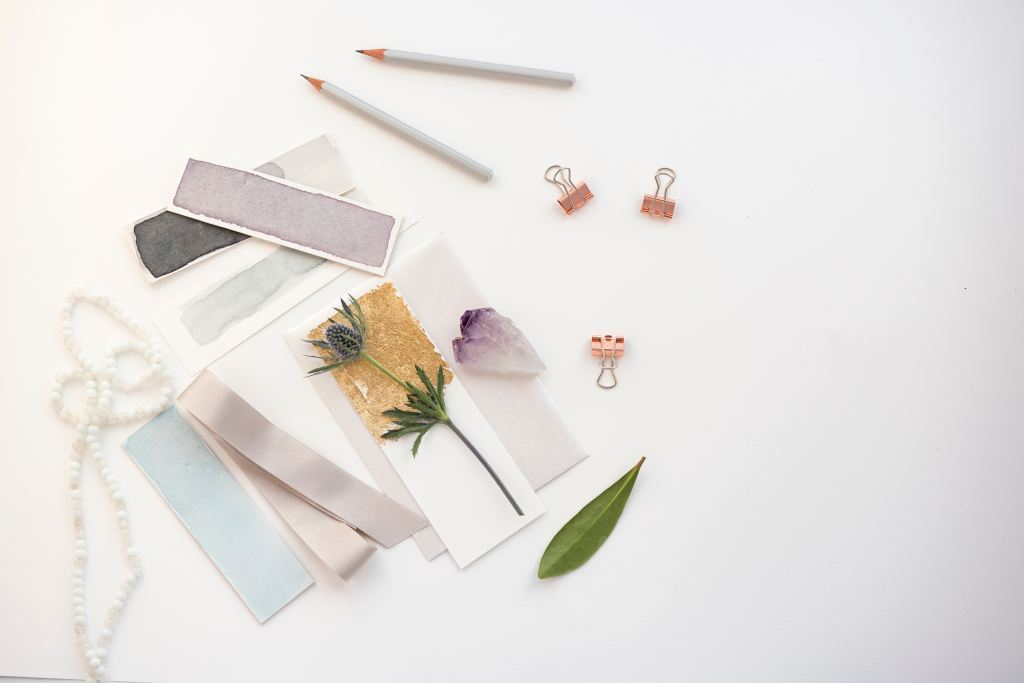 Pastel paint swatches, pencils, and botanical pieces on a white surface.