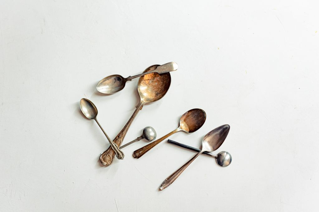 Antique spoons on a white surface.