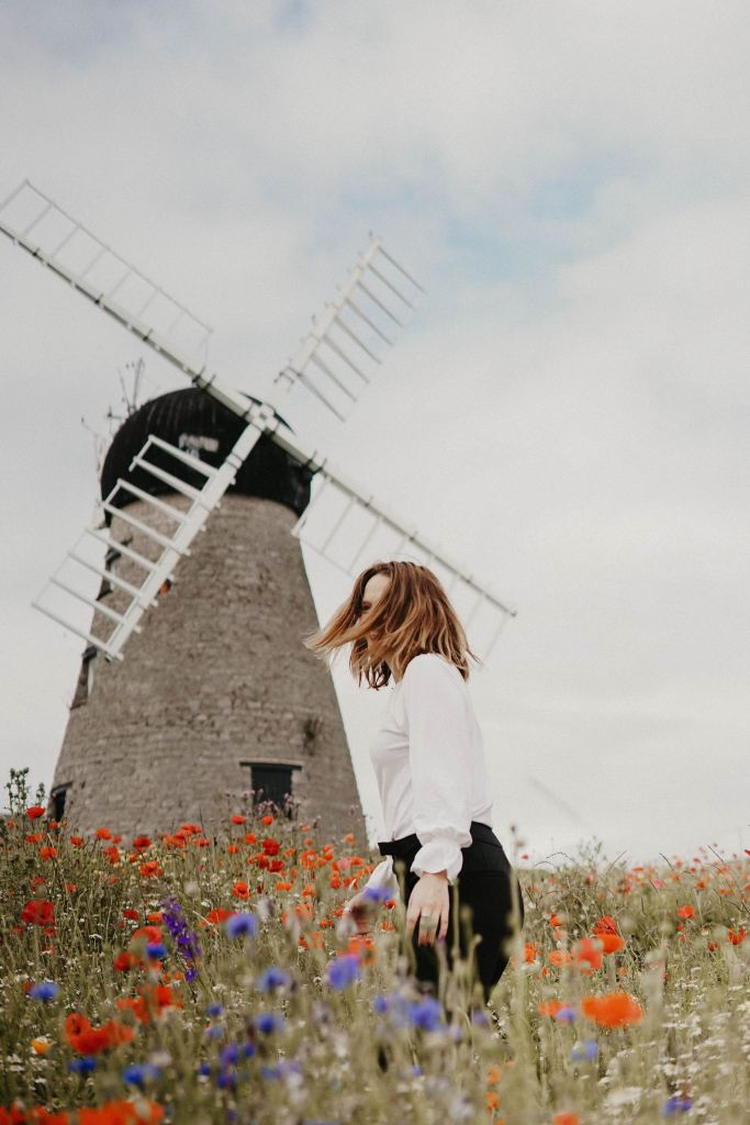 Woman standing in a field of wildflowers. A windmill made of stone stands behind her.