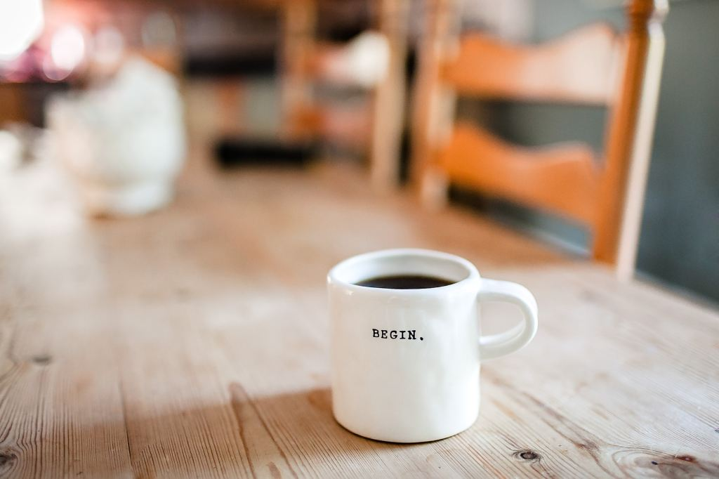 White coffee mug with the word Begin on it sitting on a wooden table.