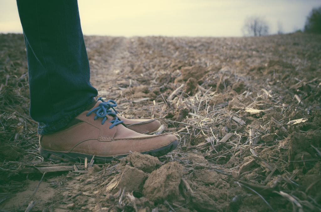 Man standing in a barren field wearing brown boots.