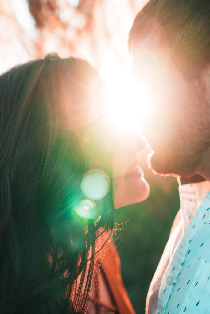 A couple standing closely about to kiss. The sun blurs out the faces.
